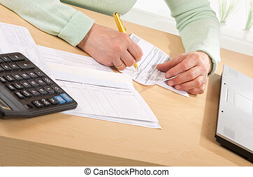 mature woman fill in receipt - Hands of mature woman fill in...
