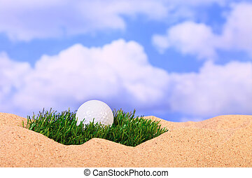 Golf ball on a tuft of grass in bunker