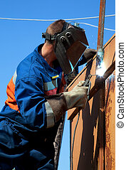 A welder working at height on a background of blue sky