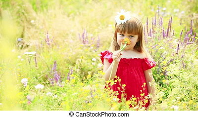 Girl smelling a yellow flower - Children outdoors