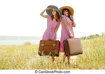 Two retro style girls with suitcases at countryside