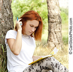 Redhead girl doing homework at outdoor.