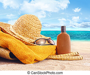 Suntan lotion, straw hat at the beach - Suntan lotion, straw...