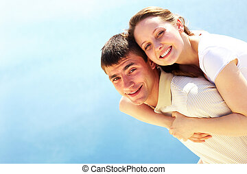 Summer mood - Photo of happy man giving piggyback to his...
