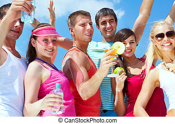 Having party - Portrait of happy young friends holding...