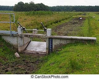 a weir in typical dutch agricultural landscape