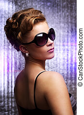 Young woman wearing sunglasses On colored background
