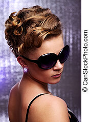 Young woman wearing sunglasses. On colored background