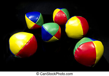 juggling balls in bright colors on black background
