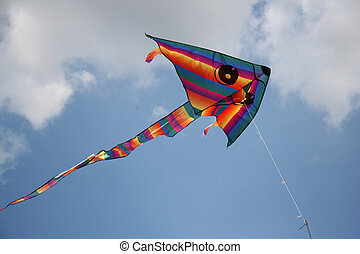 Kite in the sky - Multicolored kite with tail in blue sky