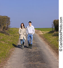 Couple of young people walking in the campaign in spring