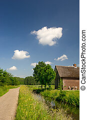 Dutch dike with ditch and house - Dutch landscape with dike...