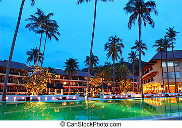 Green swimming pool near open-air restaurant in night illumination, Koh Chang island, Thailand