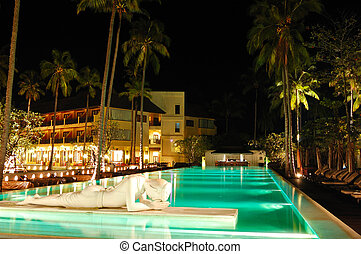 Modern swimming pool decorated with Buddha statue in night illumination, Koh Chang island, Thailand