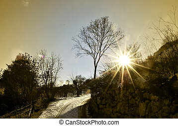 mountain road - sunset with sun on snowy mountain road