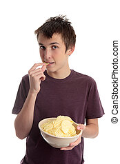 Boy eating potato crisps - A boy eating crinkle cut potato...