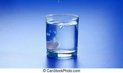 Effervescent tablet being dropped into glass of clean water...