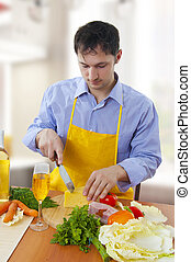 Single Man cooking in light modern kitchen