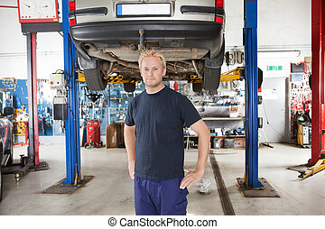 Mechanic in auto repair shop - Portrait of smiling young...