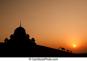 mosque in desert with camels silhouette