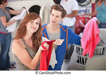 Dyed Clothing Problem - Upset man and woman with stained...