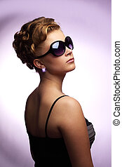 Young woman wearing sunglasses On purple background