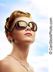 Young woman wearing sunglasses Sky background