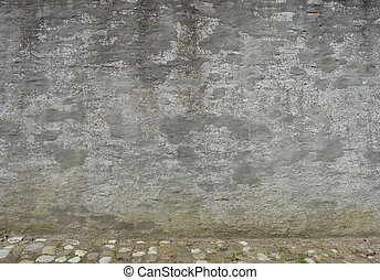 old worn gray concrete wall with cobble street