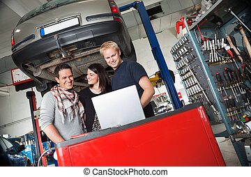 Couple in auto repair shop standing with mechanic - Young...