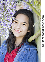 Beautiful young teen girl standing under wisteria vines -...