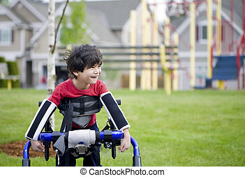 Disabled four year old boy standing in walker near a...