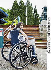 Young girl in wheelchair in front of stairs - Young nine...