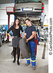 Mechanic Showing Tire to Customer - Full length portrait of...