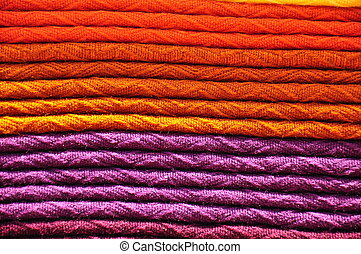 Stack of traditional woven alpaca blankets in orange and...