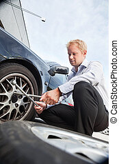 Flat Tire Business Man - Business man changing a tire on the...