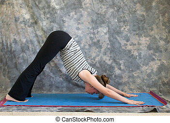 Young woman on yoga mat doing Yoga posture Adho Mukha Svanasana or Downward Facing Dog pose against a grey background in profile, facing left lit by diffused sunlight.
