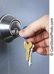 Hand inserting keys in lock - Hand inserting keys in door...