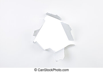 Hole in paper - Paper with ripped hole and torn edges over...