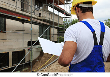 Manual worker on construction site during building...
