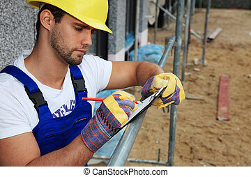 Manual worker on construction site writing on clipboard