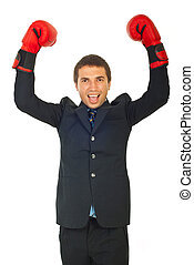 Victorious business man raising hands with boxing gloves and...