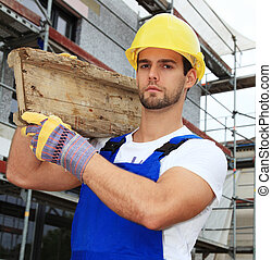 Manual worker on construction site carrying wooden board