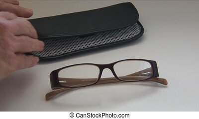 Glasses Case - A hand comes into shot and puts a pair of...