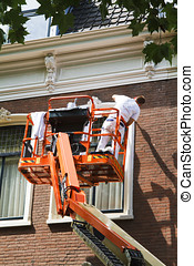 Painter on aerial access platform painting window frame