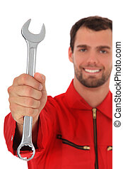 Mechanic - Smiling mechanic holding wrench. Selective focus...