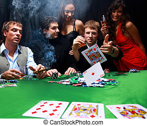 Stylish man in black suit folds two cards in casino poker at...