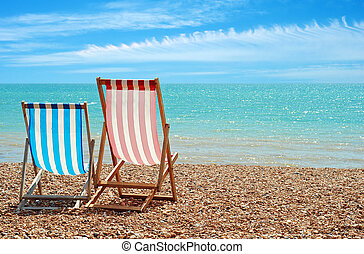beach chairs at the ocean with blue sky and clouds