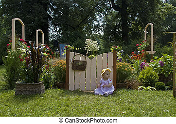 Baby sitting near miniaturized flower garden