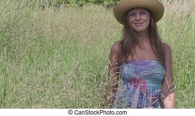 Smiling Women in Meadow - Women wearing a straw hat walks in...