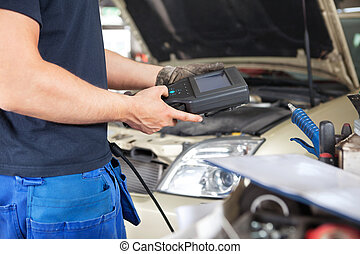 Mechanic using a Diagnostic Tool - Mid section of mechanic...